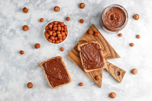 Creme de propagação ou nougat de chocolate com avelãs em frasco de vidro no concreto, copyspace
