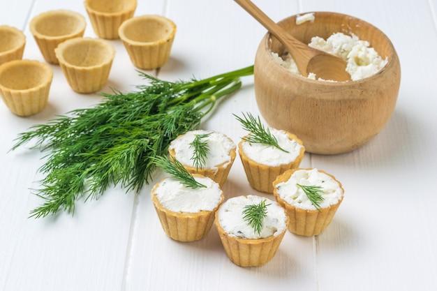 Creme de queijo cottage em uma tigela e tortinhas em uma mesa de madeira. o conceito de alimentação saudável. creme de coalhada