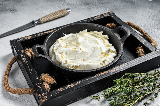 Creme de queijo mascarpone em bandeja de madeira para tiramisu. fundo branco. vista do topo.