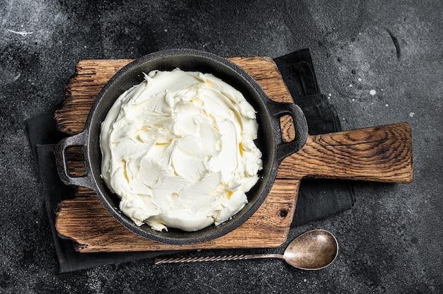 Creme de queijo mascarpone em uma panela para tiramisu. fundo preto. vista do topo.