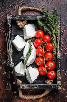 Creme de queijo ricota em uma bandeja de madeira com manjericão e tomate. fundo escuro. vista do topo.