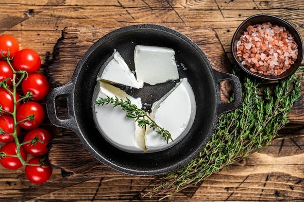 Creme de queijo ricota fresco em uma panela com manjericão e tomate. fundo de madeira. vista do topo.