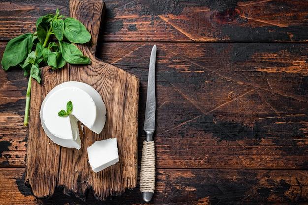 Creme de queijo ricota fresco na placa de madeira com manjericão. fundo de madeira escuro. vista do topo. copie o espaço.