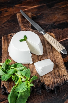 Creme de queijo ricota fresco na placa de madeira com manjericão. fundo de madeira escuro. vista do topo.