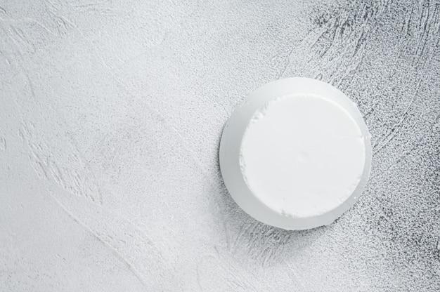 Creme de queijo ricota na mesa da cozinha. fundo branco. vista do topo. copie o espaço.