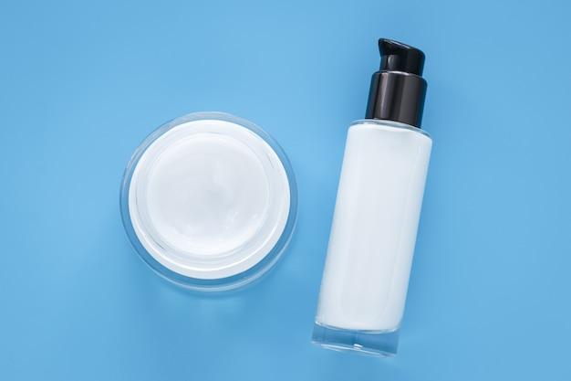 Creme de rosto em frasco de vidro e loção branca em um recipiente sobre fundo azul. conceito cosmético natural. cuidados com a pele em dermatologia.