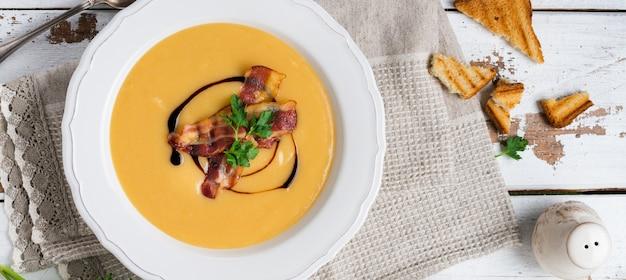 Creme de sopa de batata com bacon e molho de soja em uma tigela branca, na luz de fundo de madeira velha. vista do topo.