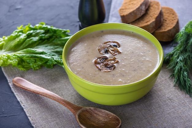 Creme de sopa de cogumelos em uma tigela verde em cima da mesa. prato tradicional vegetariano outono