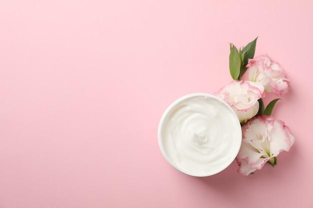 Creme e lindas flores sobre fundo rosa, espaço para texto