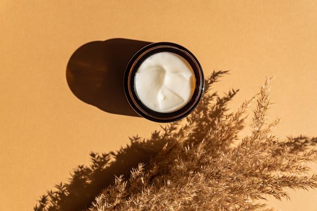 Creme facial anti-envelhecimento de colágeno em frasco de vidro escuro com palheta de orelhas secas ou pampas em fundo bege com espaço de cópia. conceito de beleza cosmética orgânica natural.
