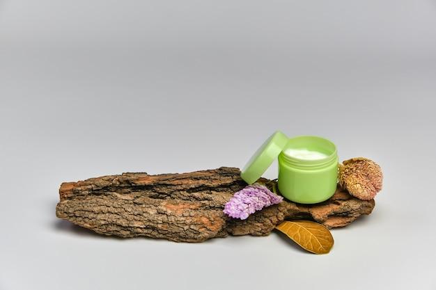 Creme facial em frasco verde na casca de árvore com flores secas, fundo branco. conceito de cosméticos naturais.