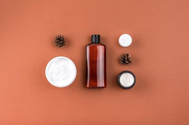 Creme hidratante de máscara facial em frasco aberto, frasco de maquete de loção. produtos para a pele com ingredientes naturais na superfície marrom.
