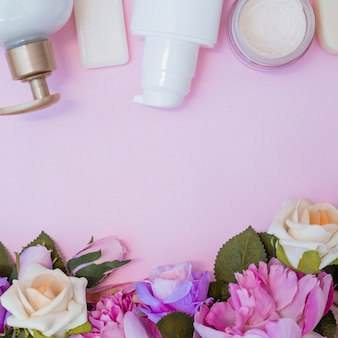 Creme hidratante e flores falsas na superfície rosa