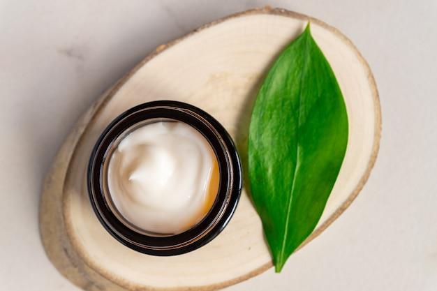 Creme hidratante natural em frasco de vidro escuro sobre placa de madeira com folha verde