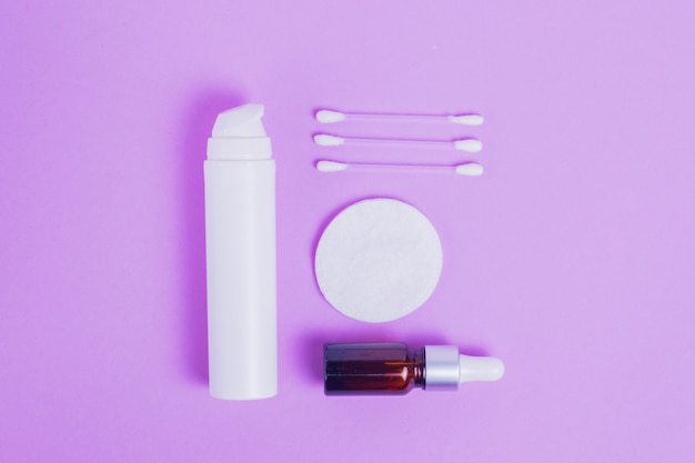 Creme hidratante para o rosto com colágeno e mucina de caracol para a pele do rosto contra rugas e acne em embalagem branca com bomba e soro facial em frasco de vidro com palitos de maquiagem