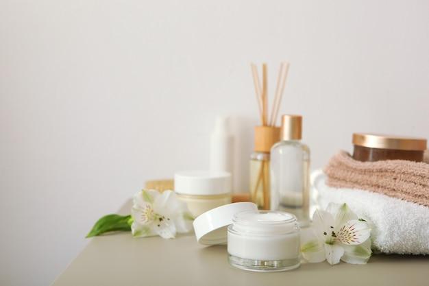 Creme para a pele e flores na mesa, cosméticos para cuidar da pele