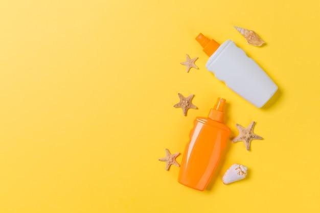 Creme protetor solar com estrelas do mar e conchas em frascos em fundo amarelo, vista superior