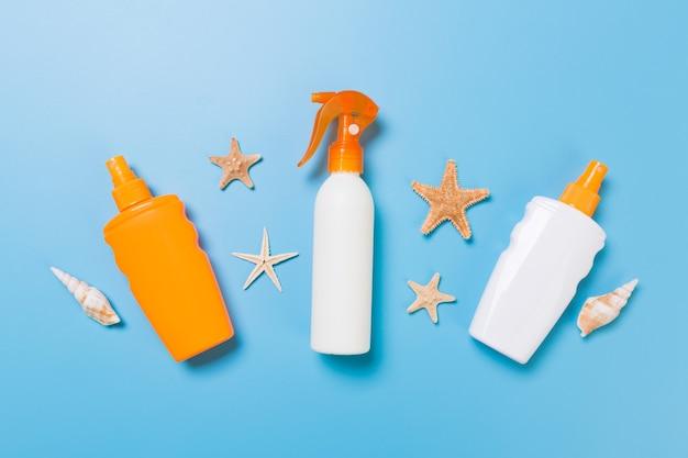 Creme protetor solar com estrelas do mar e conchas em frascos em fundo azul, vista superior