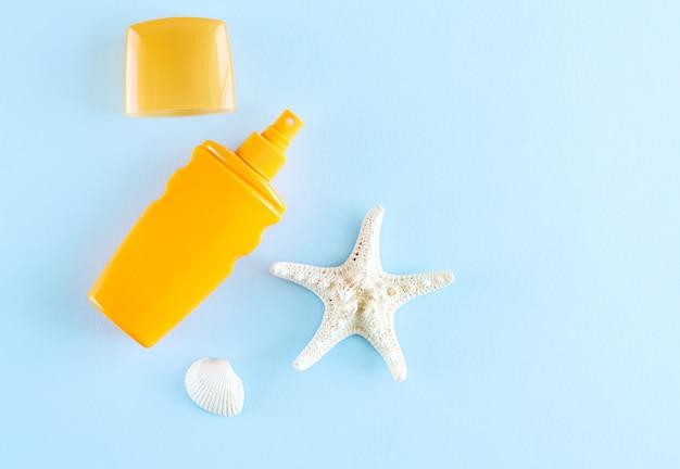 Creme protetor solar de verão ou spray próximo à concha do mar e estrela do mar na vista superior do fundo azul