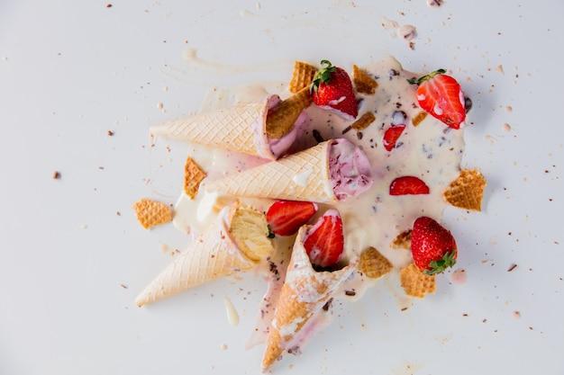 Creme quebrado e derramado, sorvete de morango e chocolate na superfície branca. acima vista