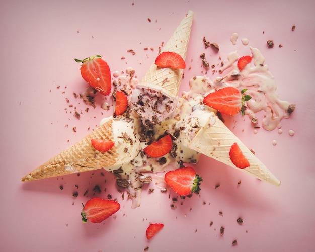 Creme quebrado e derramado, sorvete de morango e chocolate na superfície rosa. acima vista
