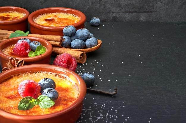 Creme queimado com frutas e ingredientes na pedra escura, espaço