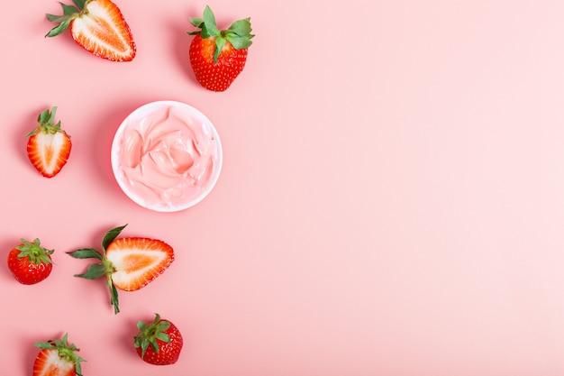 Creme rosa ou máscara facial, morangos maduros frescos em um fundo rosa. conceito de beleza. o conceito de cosméticos naturais. postura plana, copie o espaço.