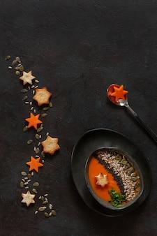 Creme-sopa caseiro da abóbora tradicional com sementes e biscoitos.