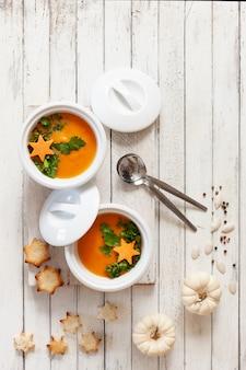 Creme-sopa caseiro tradicional da abóbora com sementes, biscoitos e as abóboras pequenas.