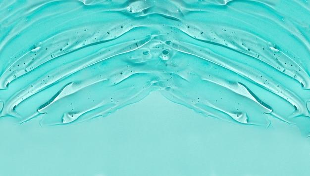 Creme transparente líquido claro cosmético. produto de cuidados com a pele em fundo azul.