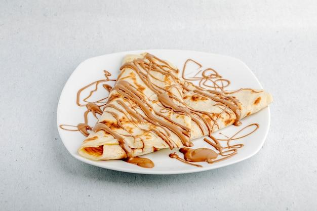 Crepe com calda de chocolate em uma placa branca em um fundo branco.