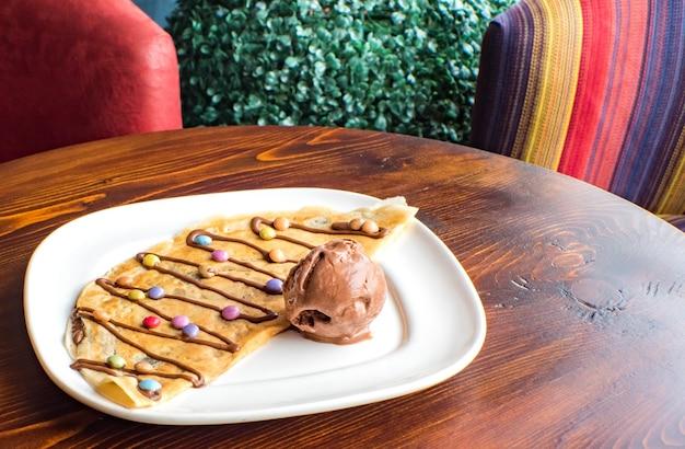 Crepe doce com creme de chocolate e sorvete no fundo de madeira