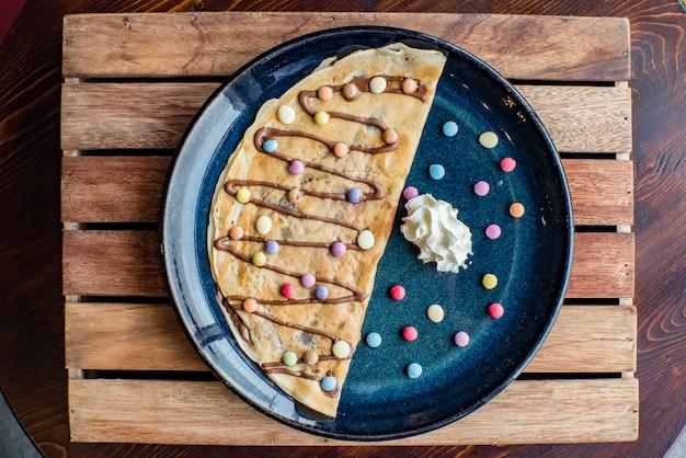Crepe doce com creme de chocolate em fundo de madeira