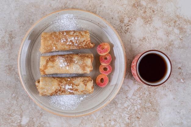 Crepes caseiros com açúcar em pó e uma xícara de chá