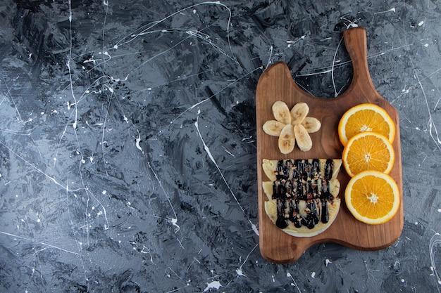 Crepes caseiros com chocolate, banana fatiada e laranja na placa de madeira.