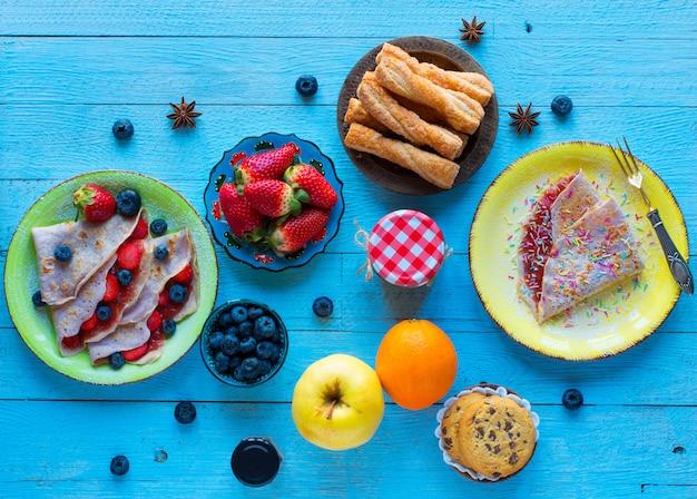 Crepes caseiros frescos, servidos em um prato com morangos e mirtilos, em um azul claro na madeira