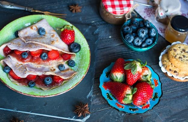Crepes caseiros frescos, servidos em um prato com morangos e mirtilos em um fundo escuro de madeira