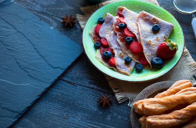 Crepes caseiros frescos, servidos em um prato com morangos e mirtilos, numa superfície de madeira escura
