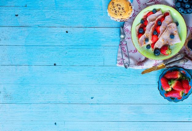 Crepes caseiros frescos, servidos em um prato com morangos e mirtilos, sobre um fundo azul claro de madeira