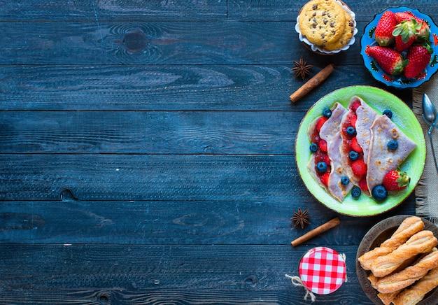Crepes caseiros frescos, servidos em um prato com morangos e mirtilos, sobre um fundo escuro de madeira,