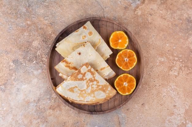 Crepes com leite servidos com rodelas de laranja em travessa de madeira