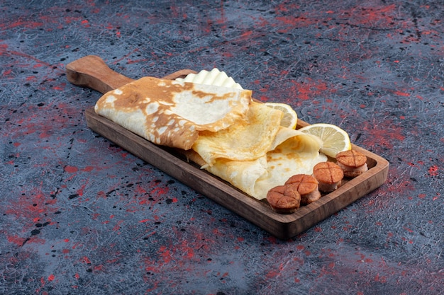 Crepes com linguiça grileld e rodelas de limão em uma travessa de madeira.