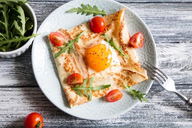 Crepes com ovos, queijo, folhas de rúcula e tomate. galette completa.