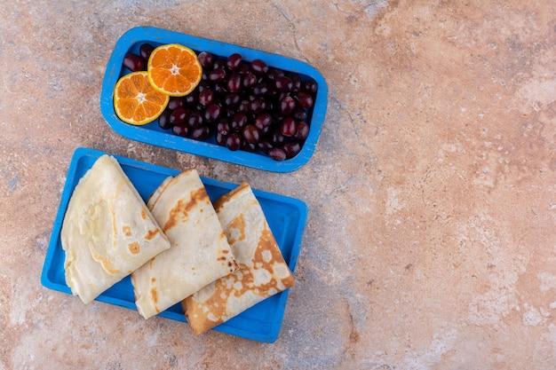Crepes com rodelas de laranja e frutas vermelhas
