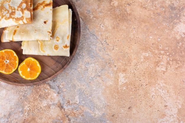 Crepes com rodelas de laranja em travessa de madeira