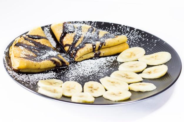 Crepes de chocolate com banana no prato, sessão de estúdio