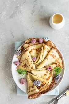 Crepes franceses caseiros (panquecas finas) com frutas congeladas e hortelã no café da manhã
