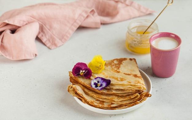 Crepes franceses, panquecas decoradas com flores, uma caneca de cappuccino e mel. conceito de café da manhã, sobremesa.