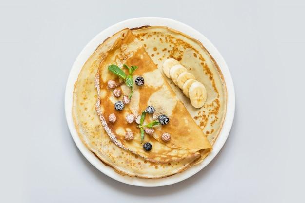 Crepes, panquecas russas finas em um prato branco.