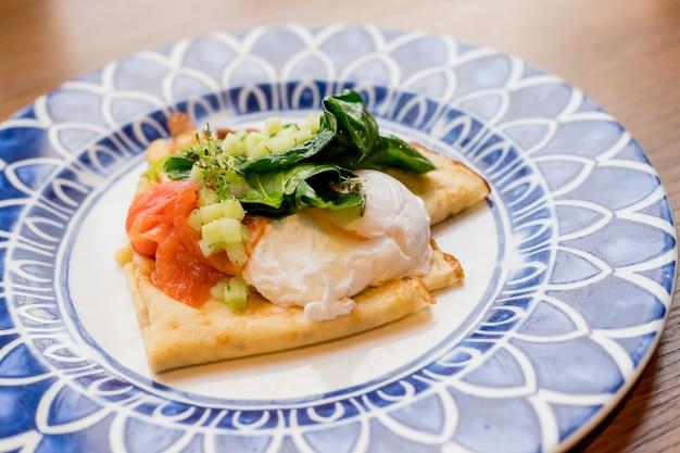 Crepes salgados com salmão e ovo escalfado. café da manhã saboroso com panquecas, salmão defumado, ovo com espinafre, alface, cebola, molho holandês. café da manhã fresco e saudável.